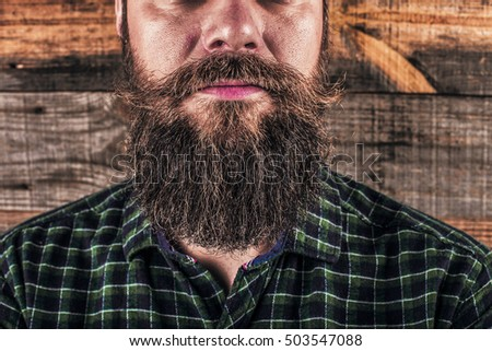 Closeup of a man beard and mustache over wooden background.Perfect beard