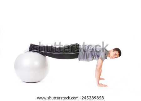 Closeup of a man doing push-ups on a white fitness ball