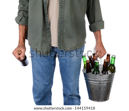 Closeup of a man in jeans carrying a bucket of beer in one hand and a single bottle in the other. Man is unrecognizable, torso and legs only, isolated on white. - stock photo