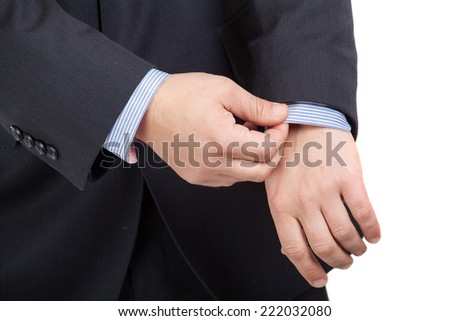 Closeup of a man in suit correcting a sleeve