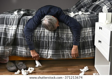 Closeup of a man laying across his bed sick with the flu unable to get up to go to work. Used tissues are strewn about the bed and floor. - stock photo