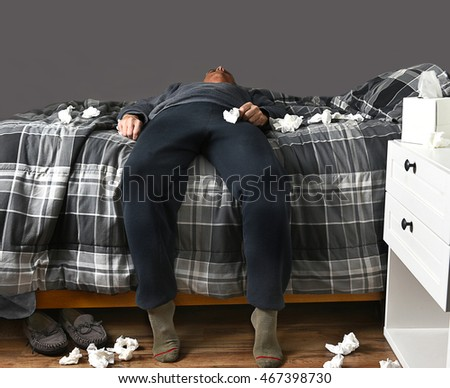 Closeup of a man laying across his bed with feet on the floor sick with the flu unable to get up to go to work. Used tissues are strewn about the bed and floor.