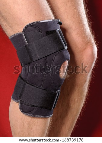 Closeup of a man legs with one knee in a protective knee brace