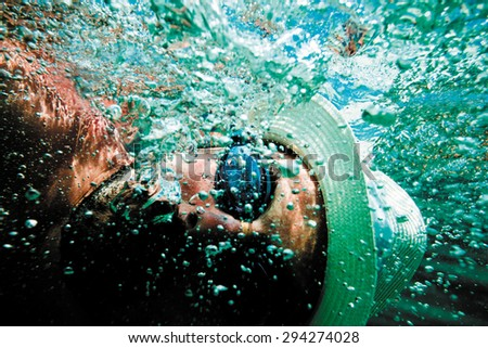 Closeup of a man's face with swimming goggles and a hat underwater in a see with a lots of bubbles around.