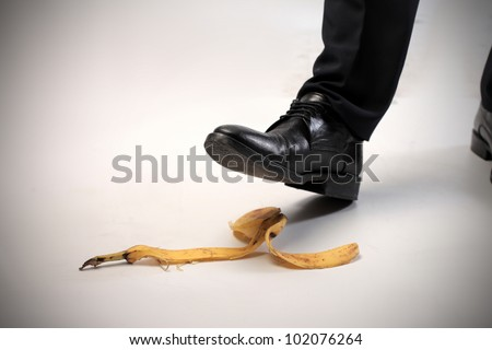 Closeup of a man's foot about to slip on a banana skin - stock photo