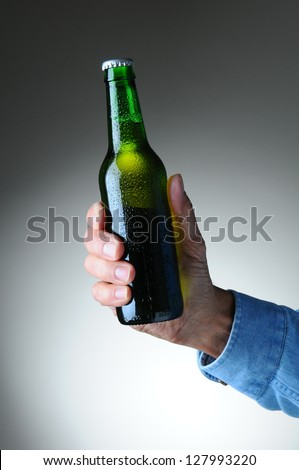 Closeup of a man's hand holding a green beer bottle over a light to dark gray background. Vertical format. Bottle has no label and is covered with condensation. - stock photo