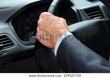 Closeup of a man's hand holding onto the steering wheel of his car. Horizontal format. Car and Driver are unrecognizable. - stock photo