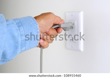 Closeup of a man's hand inserting an electrical plug into a wall socket.