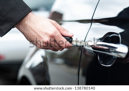 Closeup of a man's hand inserting key into the door lock of a car. - stock photo