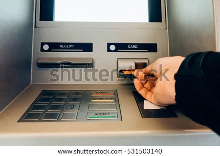 Closeup of a man's hand using an ATM