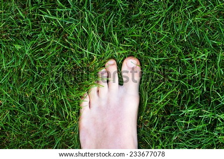 Closeup of a man's left foot standing in the lawn. - stock photo