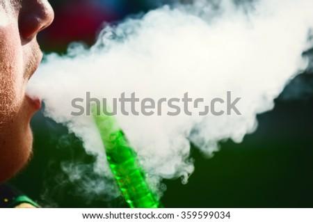Closeup of a man smoking a hookah - stock photo