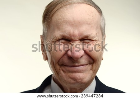 Closeup of a man squinting and smiling - stock photo