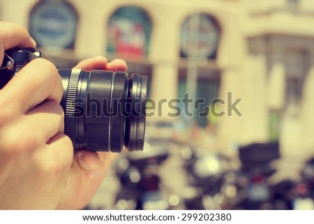 closeup of a man taking a picture with his camera in the street, with a filter effect - stock photo