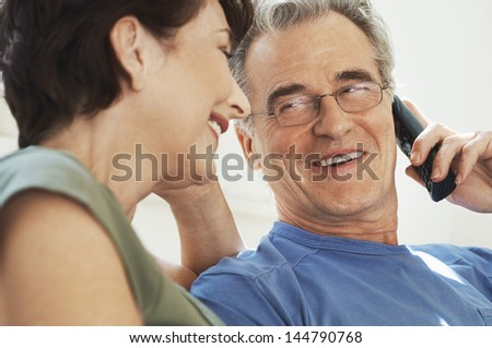 Closeup of a man using mobile phone and looking at female partner