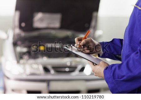 Closeup of a man writing on a clipboard in a garage - stock photo