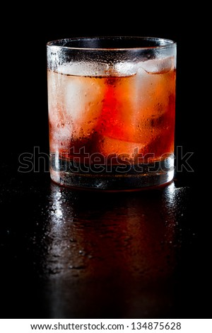 closeup of a manhattan on the rocks served on a dark bar fading in to black