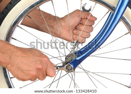 Closeup of a mans hands tightening the bolts on a bicycle wheel. - stock photo