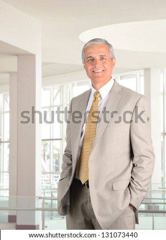 Closeup of a mature businessman standing in a modern office setting with his hands in pants pockets. Vertical format. - stock photo