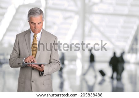 Closeup of a mature businessman using his tablet computer in an airport concourse. The man is looking at the device with blurred passengers in the background.