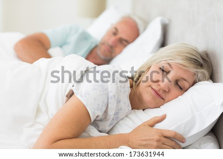 Closeup of a mature couple sleeping with eyes closed in the bed at home - stock photo