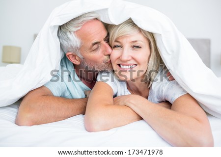 Closeup of a mature man kissing womans cheek in bed at the home - stock photo