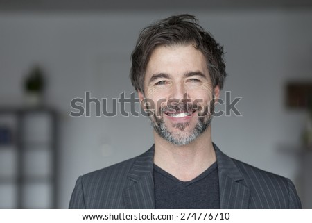 Closeup Of A Mature Man Smiling At The Camera - stock photo