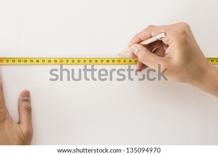 Closeup of a measuring tape and  pencil marking with a white wall