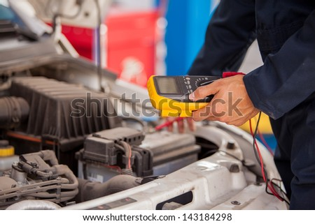 Closeup of a mechanic checking a car battery at an auto shop - stock photo