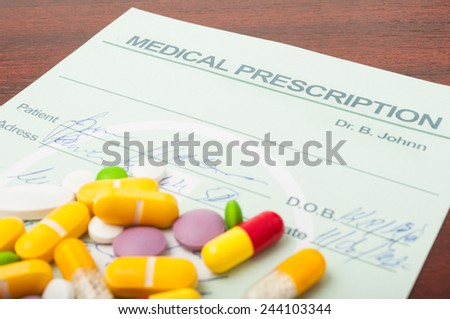 Closeup of a medical prescription with various drugs on top of it, already filled out by the doctor - stock photo