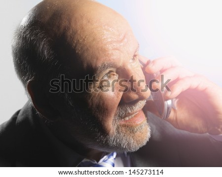 Closeup of a middle aged businessman looking into bright light while talking on mobile phone