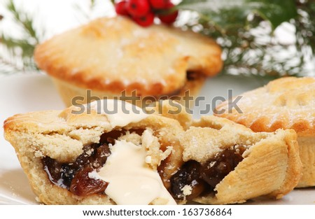 Closeup of a mince pie with cream against a soft focus background
