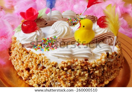 closeup of a mona de pascua, a cake eaten in Spain on Easter Monday, ornamented with feathers and a teddy chick - stock photo