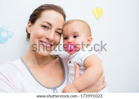 Closeup of a mother and baby with pacifier at home