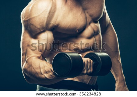 Closeup of a muscular young man lifting dumbbells weights on dark background .