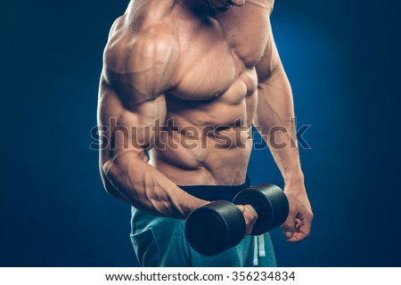 Closeup of a muscular young man lifting dumbbells weights on dark background . - stock photo