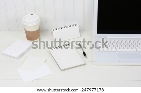 Closeup of a neat white desk with Laptop, disposable coffee cup, note pad, envelopes and pen. A wood desk with a beadboard wall behind. The image is primarily shades of white. - stock photo
