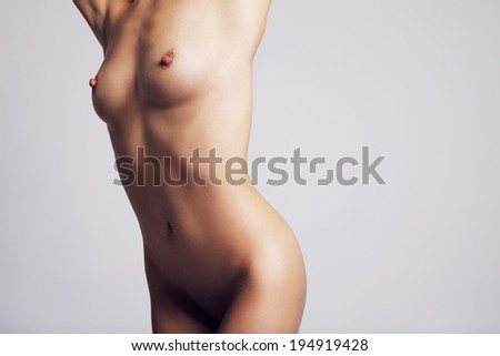 Closeup of a nude female body on grey background. Copy space right. - stock photo