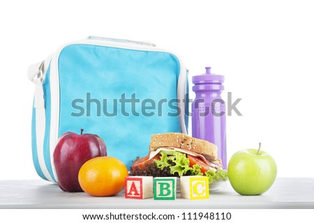 Closeup of a packed school lunch with alphabet blocks. shot in studio - stock photo