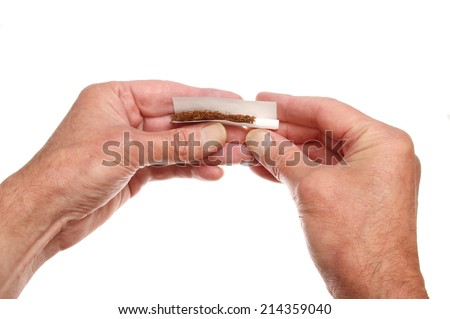 Closeup of a pair of hands rolling a cigarette isolated against white - stock photo