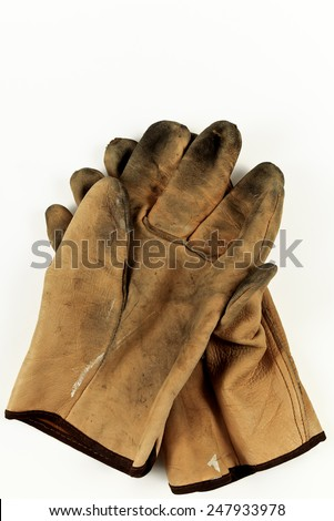 Closeup of a pair of worn leather work gloves isolated on a white background - stock photo