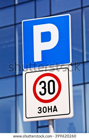 Closeup of a park and speed limit signs, building in background - stock photo