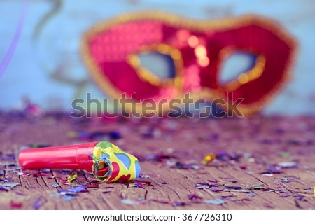 closeup of a party horn on a rustic wooden surface full of confetti and an elegant red and golden carnival mask in the background - stock photo