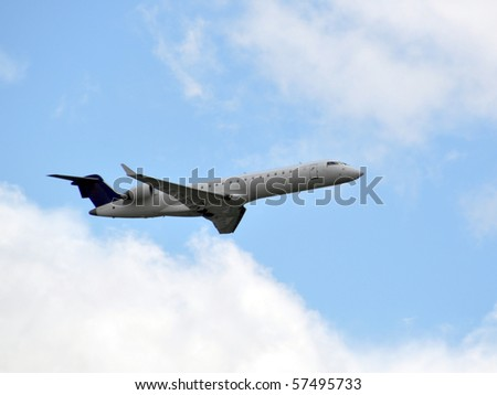Closeup of a passenger airplane taking off into a cloudy sky