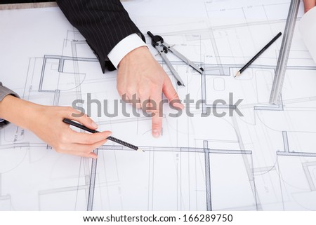 Closeup Of A Person's Hand Pointing On Blue Print - stock photo