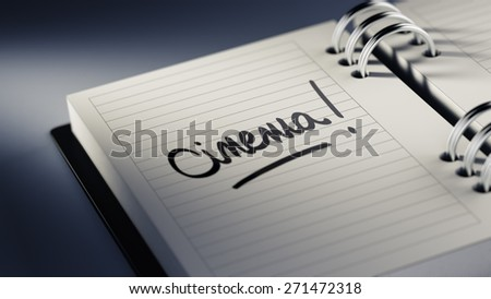 Closeup of a personal agenda setting an important date representing a time schedule. The words Cinema written on a white notebook to remind you an important appointment.