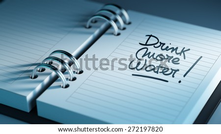 Closeup of a personal agenda setting an important date representing a time schedule. The words Drink more water written on a white notebook to remind you an important appointment. - stock photo