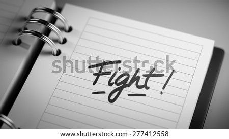 Closeup of a personal agenda setting an important date representing a time schedule. The words Fight written on a white notebook to remind you an important appointment.