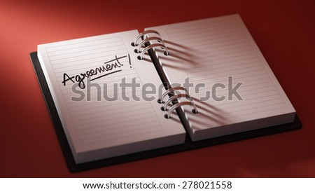 Closeup of a personal agenda setting an important date representing a time schedule. The words Agreement written on a white notebook to remind you an important appointment. - stock photo