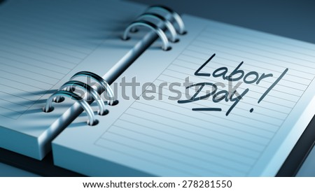 Closeup of a personal agenda setting an important date representing a time schedule. The words Labor Day written on a white notebook to remind you an important appointment.
